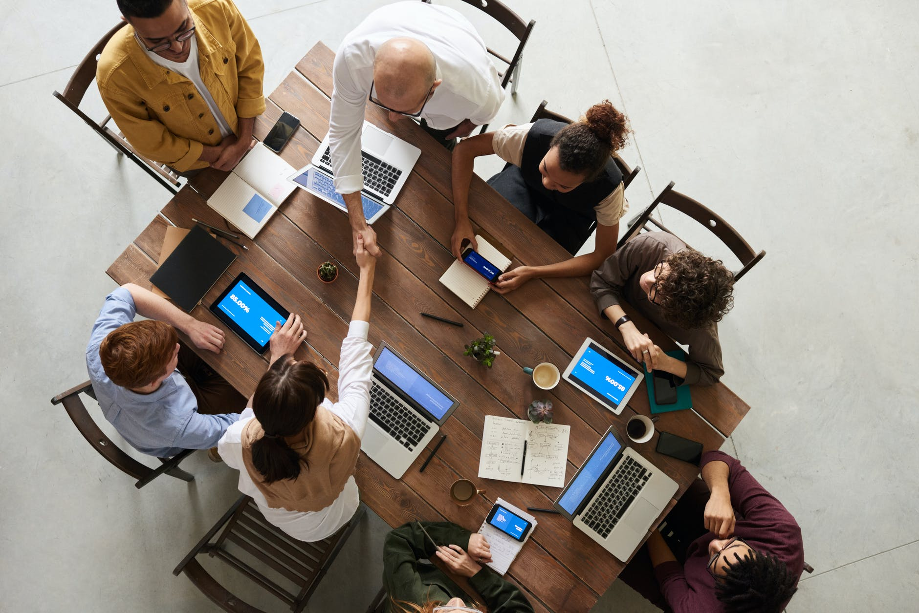 8 people using laptops and sitting around a table for professional collaboration