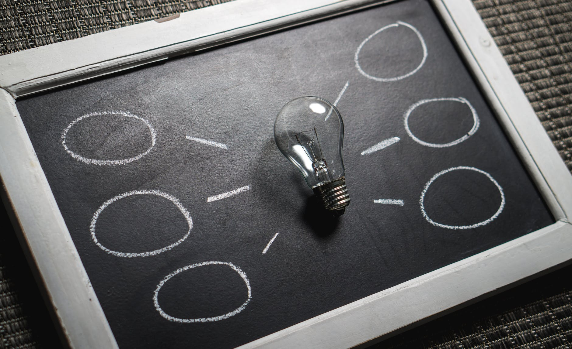 Chalk board with light bulb in the middle representing educational consultation and information