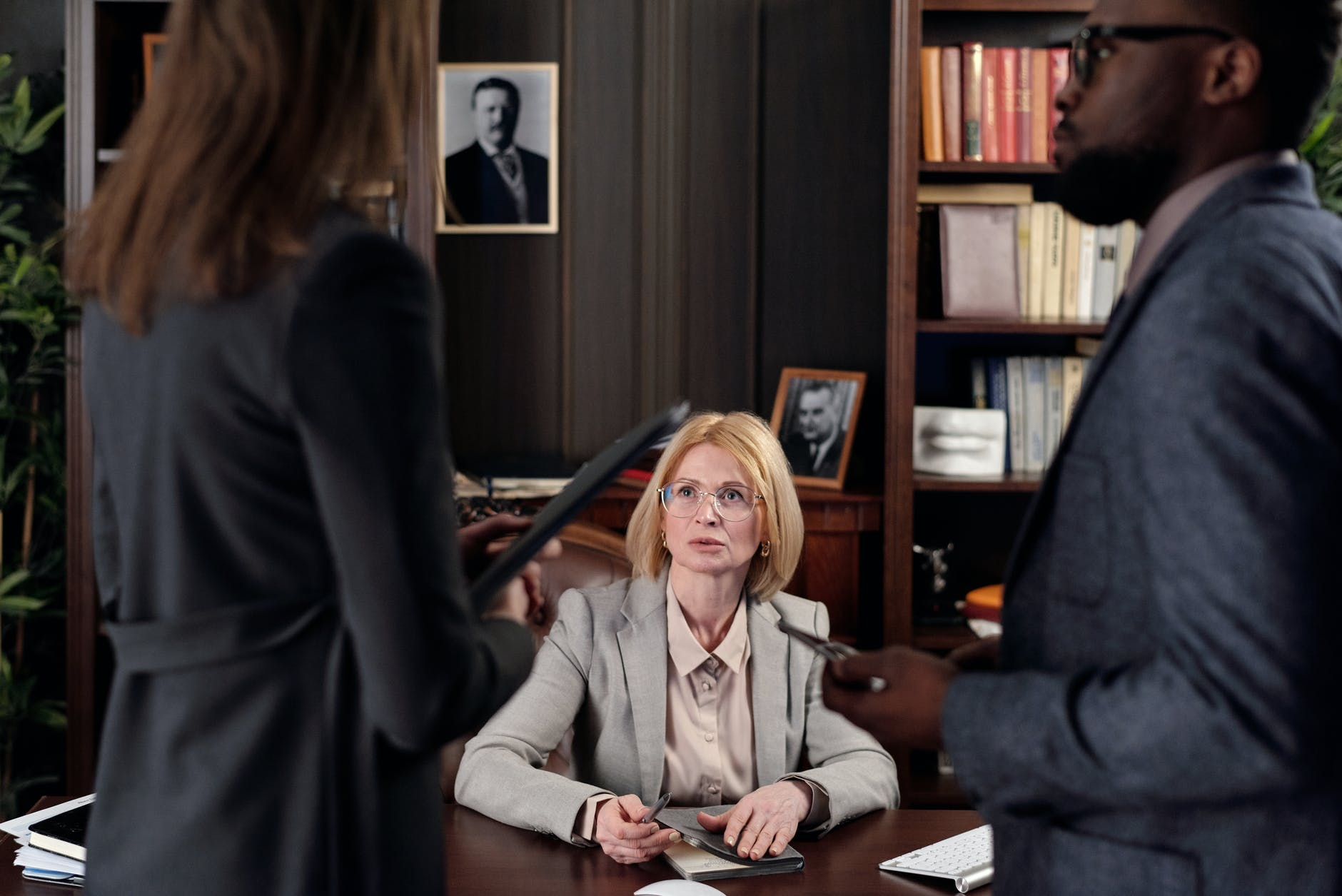 Three people having a discussion in an attorney's office