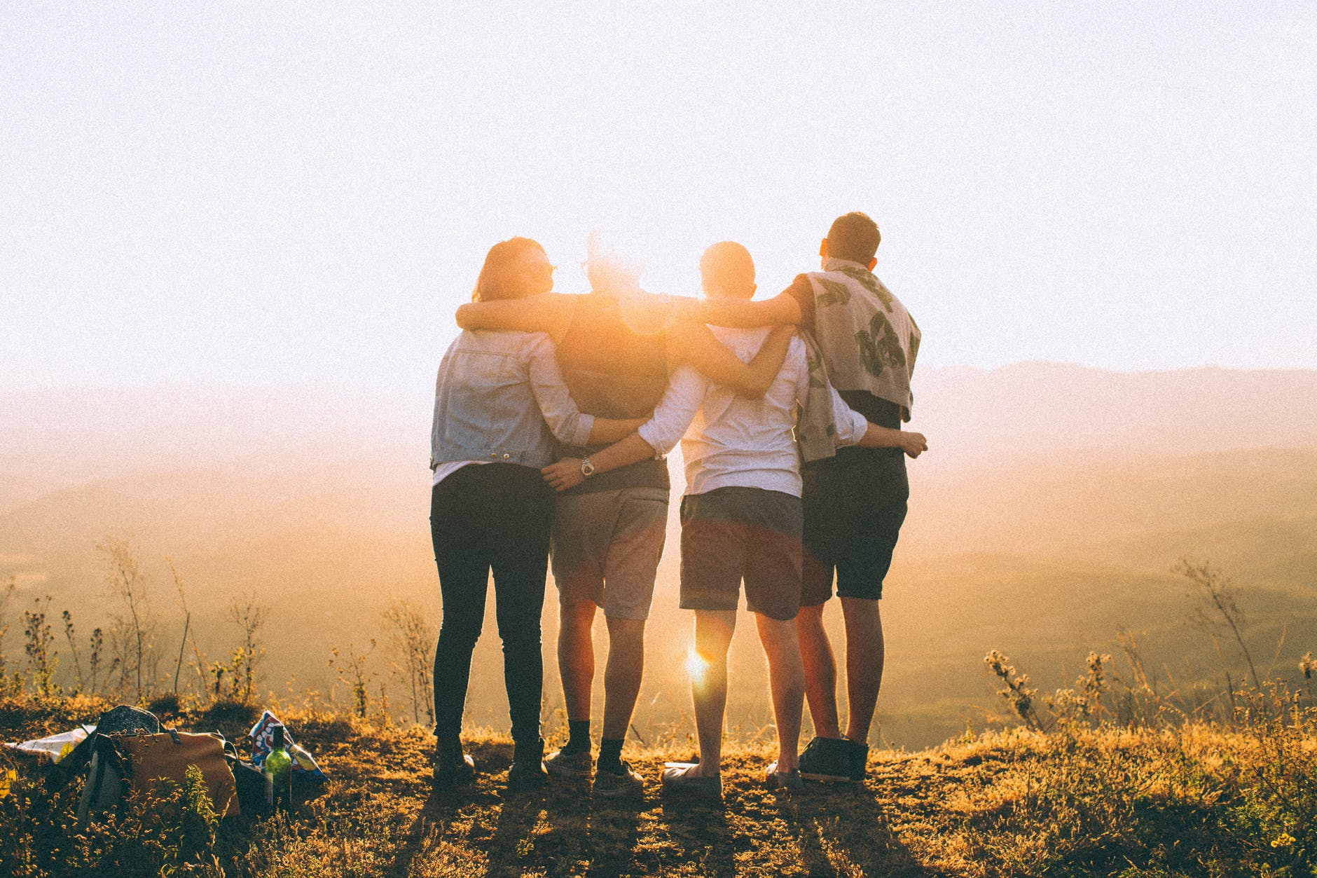 4 friends standing and looking at the sunset